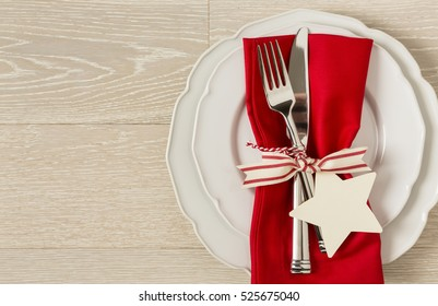 Festive Christmas table setting place setting with white china plates, red cloth napkin and silverware on rustic wood background. Horizontal with empty blank space on left.
