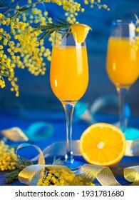 Festive cocktail mimosa in glasses, blooming mimosa branches, blue bright fountain