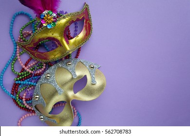 Festive, colorful group of mardi gras or carnivale mask on purple background.