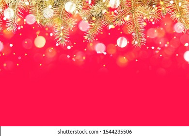 Festive composition with border of fluffy gold fir branches and golden confetti stars sparse on red background. Christmas lights bokeh. Top view, flat lay style, copy space for text.