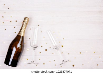 Festive composition with champagne & golden glitter. Traditional New Year celebration. Winter holiday season, christmas time concept. Greeting card mock up. Background, top view, copy space, flat lay.