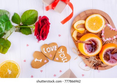 Festive composition with cookies in shape of heart with I Love you words, rose, unusual served in orange mulled wine on the white table. Valentine' s day surprize for lover. Selective focus