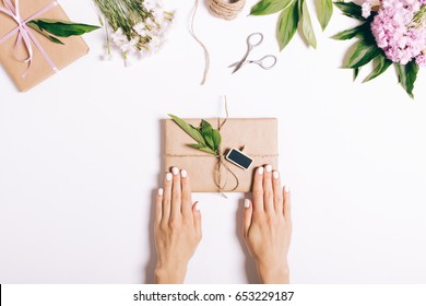 Festive composition, female hands wrapping a book for a gift, top view