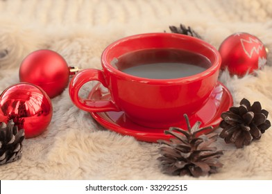 A festive and cozy composition with a red cup of hot coffee, fir cones and Christmas-tree decorations on a white fur surface