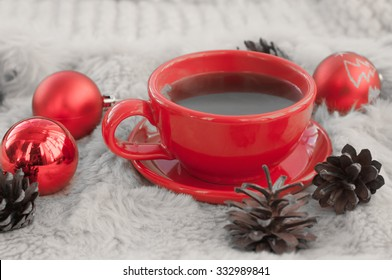 A festive and cozy composition with a red cup of hot coffee, fir twigs, cones, cinnamon sticks and Christmas tree decorations on a white fur surface; colors are processed creatively