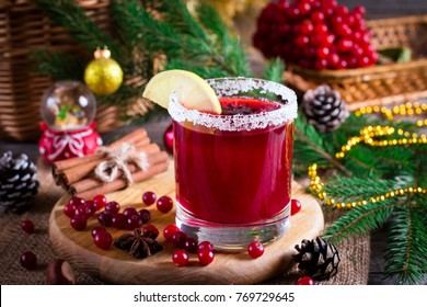 Festive Cranberry drink on Christmas background with fir branches and fresh berries, selective focus. Holiday concept.