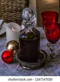 Festive crystal decanter with two red crystal glasses on table . Stock Image