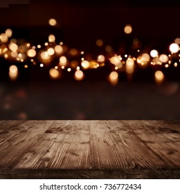 Festive dark background with golden light effects and empty wooden table for a christmas decoration