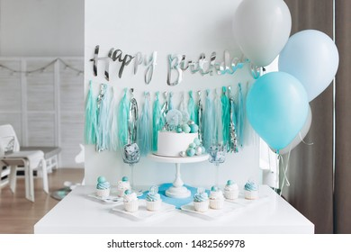 """festive decor in honor of one year old baby boy.  white cake on a stand, cupcakes, blue balls and tinsel.  the inscription """"happy birthday"""""""