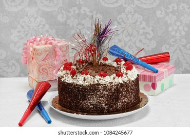 A festive, decorated  black forest chocolate birthday cake with gifts and party horns