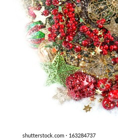 festive decoration with baubles, golden garlands, christmas tree and red berries branches. holidays background with falling snow effect