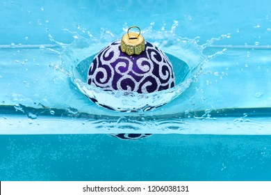 Festive decoration for Christmas tree, violet ball dropped into water with splashes, blue background. Christmas decoration or toy for Christmas tree swim in pool. Holidays and vacation concept.