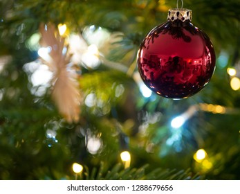 Festive Decoration hanging on a christmas tree, with lights blurred in background