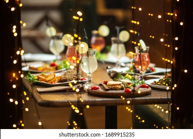 Festive dinner, served table, cocktails, delicious dishes, side view, horizontal