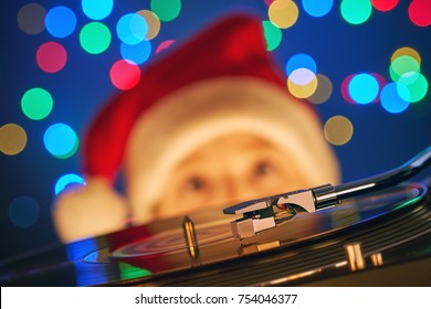 Festive dynamic postcard. A happy boy in Santa's red cap looks at the spinning vinyl record on the turntable player on a blurred background of a bright Christmas garland. Happy New Year. Christmas eve