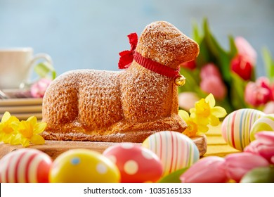 Festive Easter table with a novelty lamb cake tied with a red ribbon surrounded by colored eggs, spring daffodils and tulips