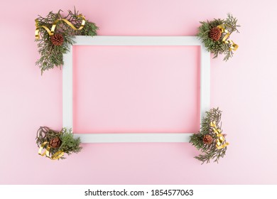 Festive elegant background. Blank photo frame on pastel pink background with fir tree twigs Christmas, New Year, birthday concept. Flat lay, top view, copy space