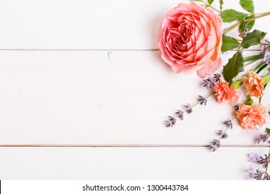 Festive English rose, lavender and wild spring summer flowers composition on white wooden background. Overhead top view, flat lay. Copy space. Birthday, Mother's, Women's, Wedding Day concept