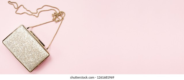 Festive evening golden clutch on pink. Holiday and celebration background. Luxury accessories and party concept. Horizontal, wide screen banner format