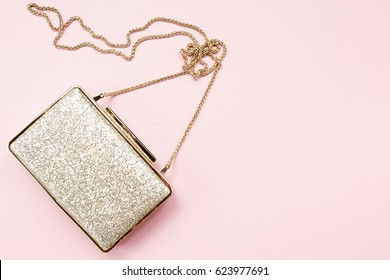 Festive evening golden clutch on pink. Holiday and celebration background. Luxury accessories and party concept. Horizontal