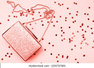 Festive evening golden clutch with star sprinkles on pink. Holiday and celebration background. Luxury accessories and party concept. Horizontal. Living coral theme - color of the year 2019