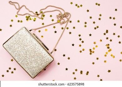 Festive evening golden clutch with star sprinkles on pink. Holiday and celebration background. Luxury accessories and party concept. Horizontal