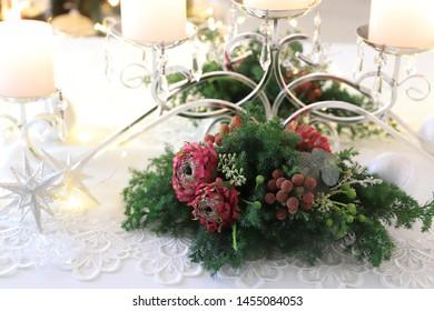 Festive evergreen flower arrangement with candles