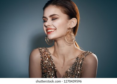 festive fashion woman in gold dress with earrings smiling