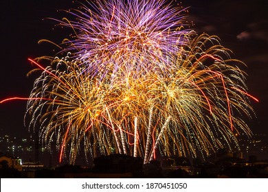festive fireworks in the dark night sky over the city. pyrotechnic product. Christmas beautiful fireworks. lights show.