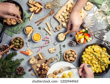 Festive flat lay with christmas dinner party table and human hands, holiday vegeterian food concept background, top view
