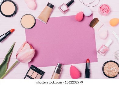 Festive flat layout of decorative cosmetics and accessories on wooden background with empty space for text. Feminine beauty products and fresh flower on pink table, top view.