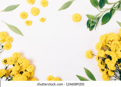 Festive floral flat lay frame of yellow flowers and green leaves on white wooden table with blank center, top view.
