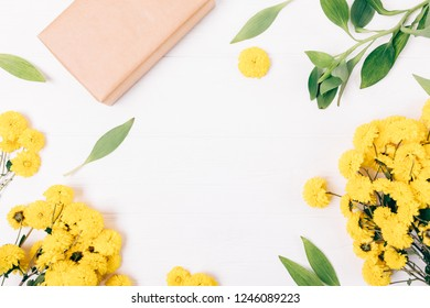 Festive floral flat lay frame of gift box, fresh yellow flowers and green leaves on white wooden table with blank center, top view.
