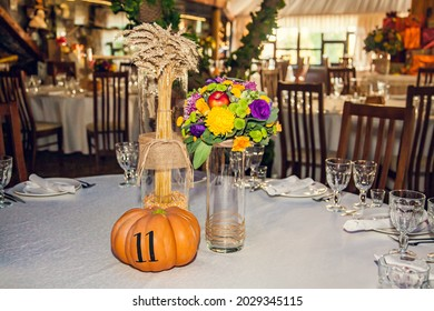 Festive floristry in autumn style with numbering of tables on pumpkins in banquet hall. Floristry and decoration of events floral arrangements.