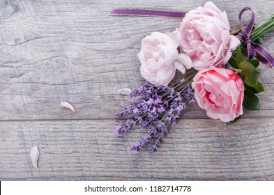 Festive flower English roses composition with ribbon, lavender on wooden background, rustic style. Overhead top view, flat lay. Copy space. Birthday, Mother's, Valentines, Women's, Wedding Day concept