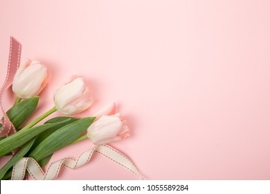 Festive flower pink tulips composition with ribbon on the light pink background. Overhead top view, flat lay. Copy space. Birthday, Mother's, Valentines, Women's, Wedding Day concept.