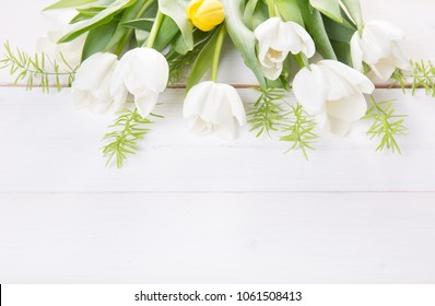 Festive flower white tulips composition on white wooden desk, background. Overhead top view, flat lay. Copy space. Birthday, Mother's, Valentines, Women's, Wedding Day concept.