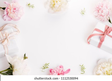 Festive flowers pink and white peony, gift with ribbon composition on the white background. Overhead top view, flat lay. Copy space. Birthday, Mother's, Valentines, Women's, Wedding Day concept.