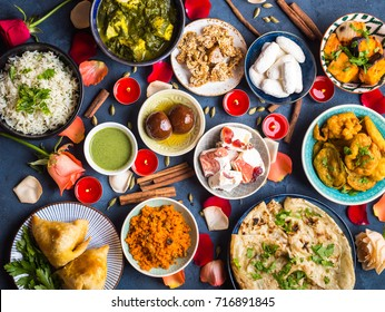 Festive food for Indian festival Diwali. Naan, samosa, rice, paneer, sweets. Holiday Indian table with food, sweets, flowers, burning candles. Diwali celebratory dinner. Assorted Indian dishes, snacks