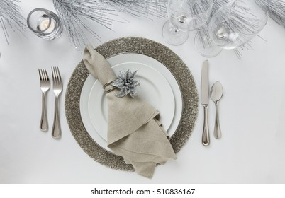 Festive formal fine dining Christmas or New Year's Eve holiday dinner party table setting place setting with white china plates, silverware, cloth napkin, wine glasses and silver glitter decorations