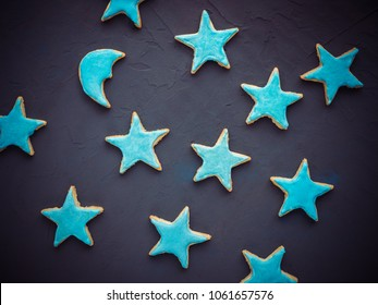 Festive, fragrant cookies in the shape of the stars and the moon, covered with turquoise glaze on a dark, textured surface