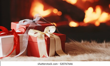 Festive Gift Boxes standing by the Burning Fireplace - Close Up. Decorated present with ribbon by the warm cozy fireside. Christmas and Winter Holidays Background