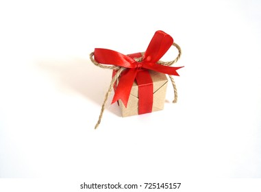 A festive gift. One box with a gift. A Christmas gift. New Year's surprise. Gift in the box. Ribbon, bow and paper. Colors red kraft, brown, green. White background.