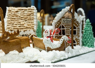 Festive Gingerbread village with marzipan santa in sleigh