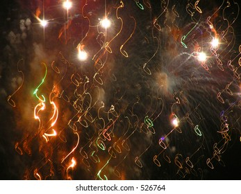 Festive glowing purple and green fireworks create shape of musical notes as they dance in the black night sky