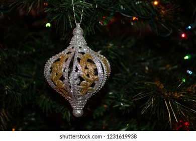 Festive Gold and Silver Christmas Ornament hanging on an evergreen tree