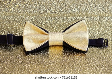 A festive golden with a black bow tie on a gold background.