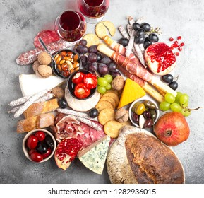 Festive gourmet mix of snacks and appetizers, cheese, meat, olives, bread, fruit, canapés, wine in glasses. Italian antipasti set or Spanish tapas bar. Food to share, party or picnic time, top view
