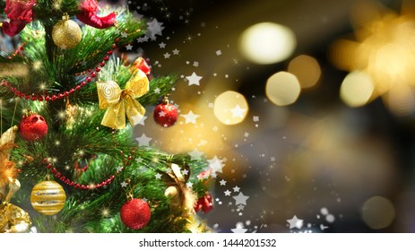 Festive green Christmas tree decorated with gold and red toys balls and bows with soft focus in evening and beautiful dark blurred defocused sparkling background with golden highlights, copy space.