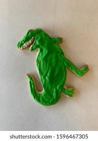 Festive green holiday sugar cookie shaped like a dinosaur. Tasty treat with monster shape.